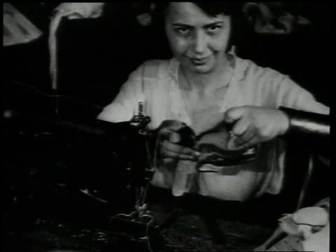 1920 ms woman sewing boxing glove at machine - anno 1920 video stock e b–roll