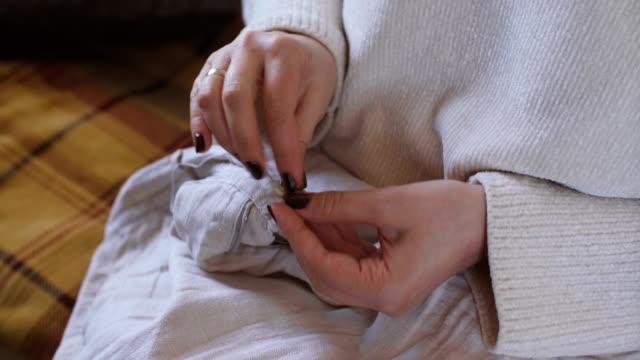 vidéos et rushes de bouton de couture femme. - coudre