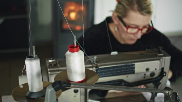 slo mo woman sewing fabric at home - dolly shot stock videos & royalty-free footage