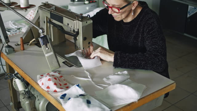 slo mo woman sewing fabric to make homemade masks - sewing stock videos & royalty-free footage