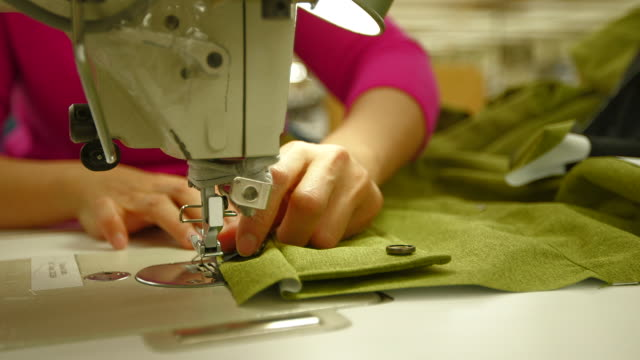CU of woman sewing zipper on coat