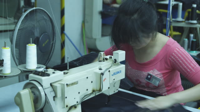 A woman sews in a factory.