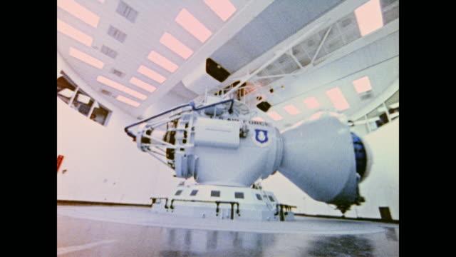 vídeos y material grabado en eventos de stock de woman sews spacesuit glove as space simulator spins astronaut and scientists gather data and prepare for spaceflight - narrar