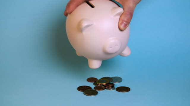 woman shakes coins out of piggy bank - coloured background stock videos & royalty-free footage