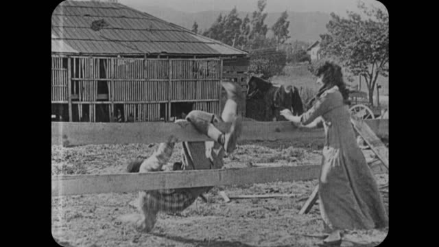 vidéos et rushes de 1916 woman (mabel normand) shakes fence until man (al st. john) falls off - clôture