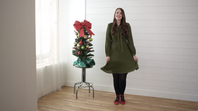 woman shaking dress next to small christmas tree - tights stock videos & royalty-free footage