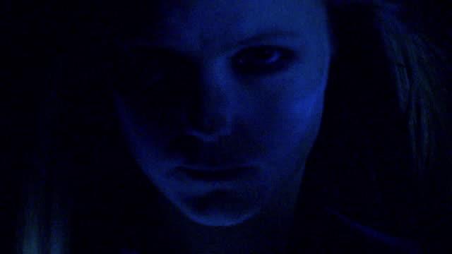 CU woman shaking head under flashing blue light in studio