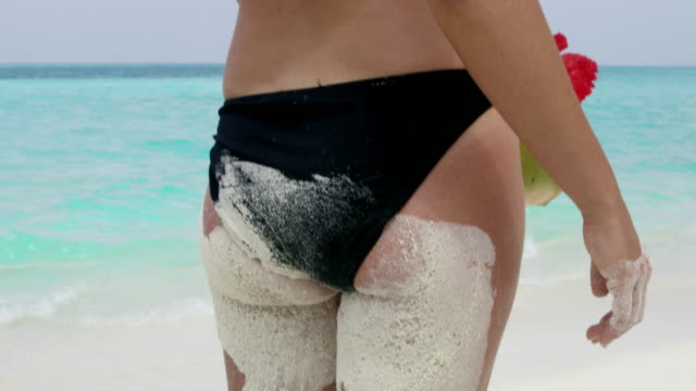 cu woman shaking sand out of bikini on sunny tropical beach,maldives - covering stock videos & royalty-free footage