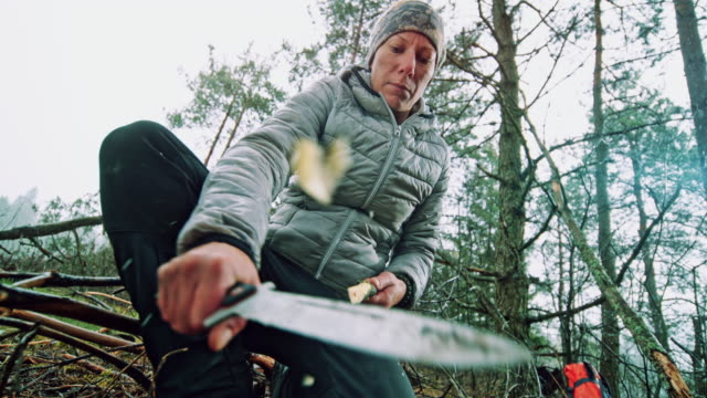 slo mo woman sharpening a branch in nature using her knife - survival stock videos & royalty-free footage