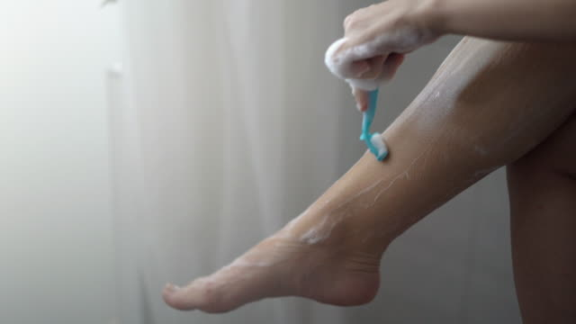 woman shaving legs under shower. - raso video stock e b–roll