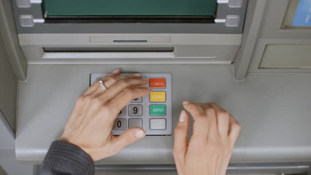 ds woman shielding the keypad on the atm as she enters her pin number - machinery stock videos & royalty-free footage