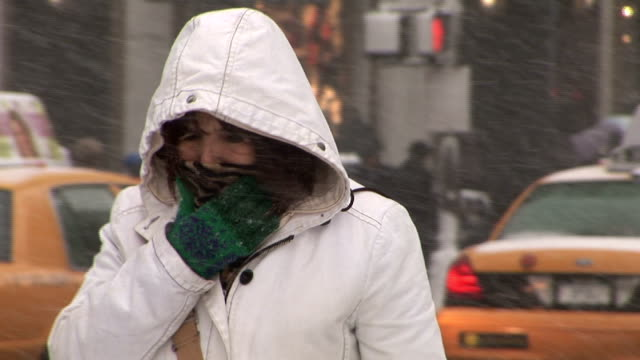 Woman shields her face from high winds and bitter cold temperatures during snow storm Manhattan