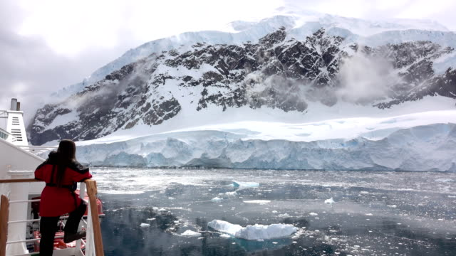 woman ship view antarctic peninsula ice filled neko harbor mountain glacier antarctica - antarctica people stock videos & royalty-free footage