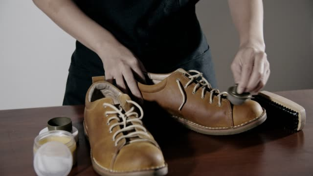 woman shoe shiner polishes the boots of brown leather with brush - animal skin stock videos & royalty-free footage