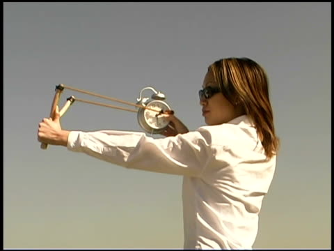 woman shooting alarm clock with slingshot - catapult stock videos & royalty-free footage