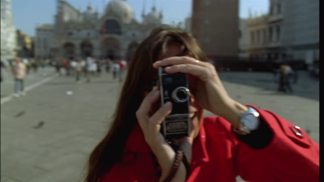 cu slo mo woman shooting film at camera with old super 8mm film camera on place san marco/ venice, italy - long stock videos and b-roll footage