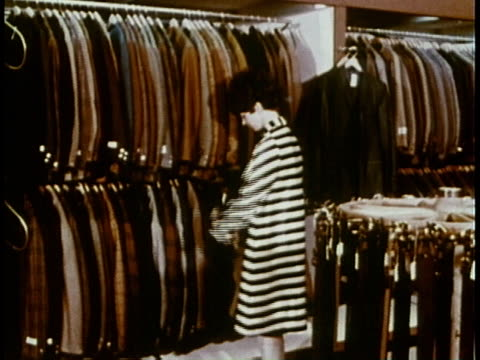 1969 WS woman shoplifter stuffing fur coat under her overcoat / United States