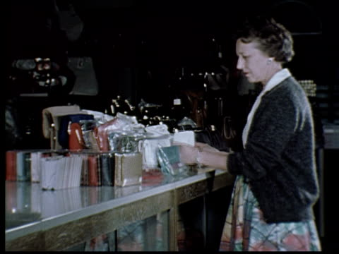 stockvideo's en b-roll-footage met 1965 ms woman shoplifting in store by putting handbags in her skirt/ berkeley, california - 1965