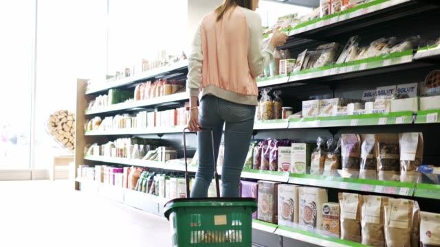 vidéos et rushes de shopper femme vérification des étiquettes sur les produits dans les supermarchés - panier courses