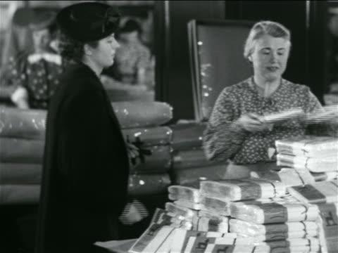 B/W 1938 woman shopper handing something to saleswoman in store / industrial