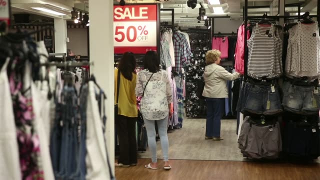 vídeos de stock, filmes e b-roll de a woman shopper pushes a shopping cart past clothing displayed for sale inside a tesco extra supermarket operated by tesco plc in london uk on... - produto interno bruto