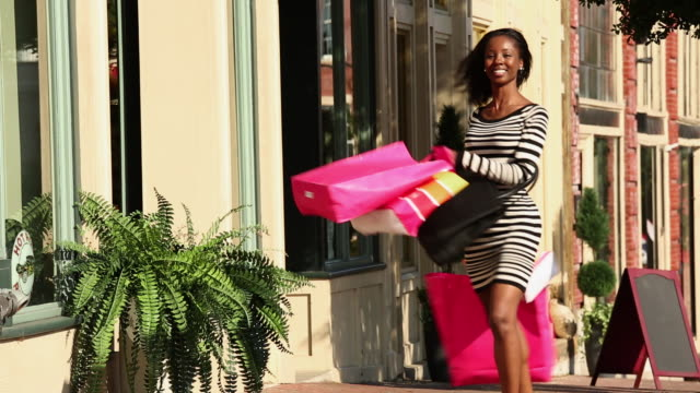 ws woman shopping and dancing in celebration in front of shop / petersburg, virginia, united states - einkaufstasche stock-videos und b-roll-filmmaterial