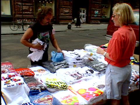 stockvideo's en b-roll-footage met woman shopping at an nyc street tshirt stand - kleding