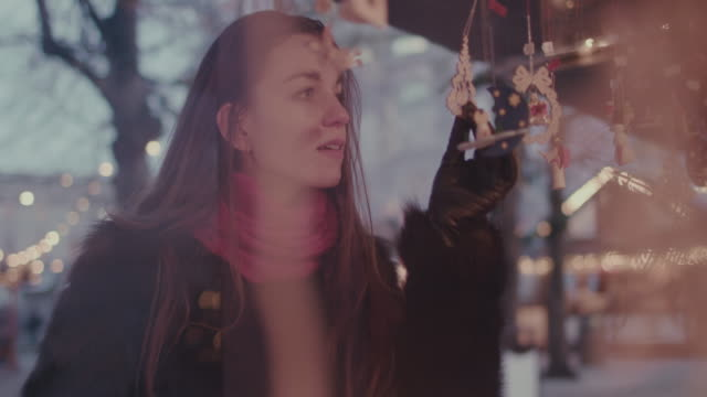 Woman shopping at Christmas market, looking at ornaments