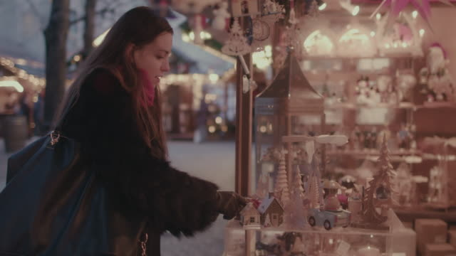 Woman shopping at Christmas market, looking at ornaments