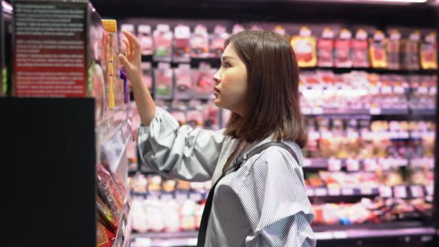vidéos et rushes de magasinage de femme à l'épicerie - panier courses