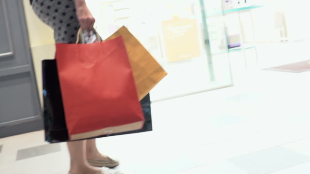 woman shopping by retail stores in slow motion. - shopping bag stock videos & royalty-free footage