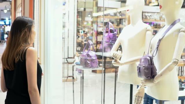 vídeos de stock, filmes e b-roll de mulher às compras por lojas de varejo em câmera lenta. - olhando vitrines