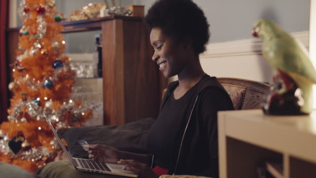 vídeos de stock, filmes e b-roll de woman shopping christmas presents online from home - finanças domésticas