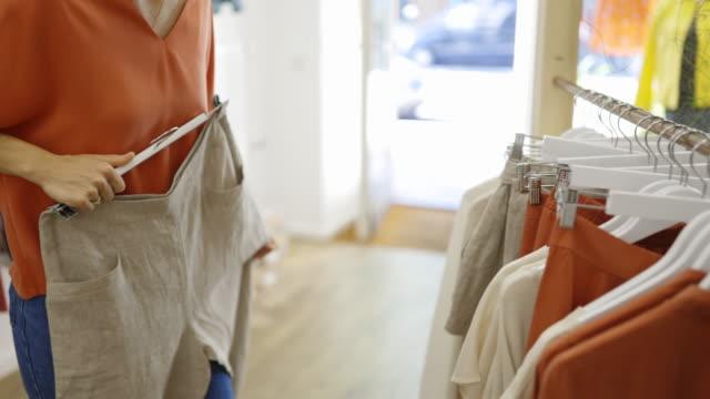 stockvideo's en b-roll-footage met de winkelende kleren van de vrouw in manieropslag - kledingwinkel