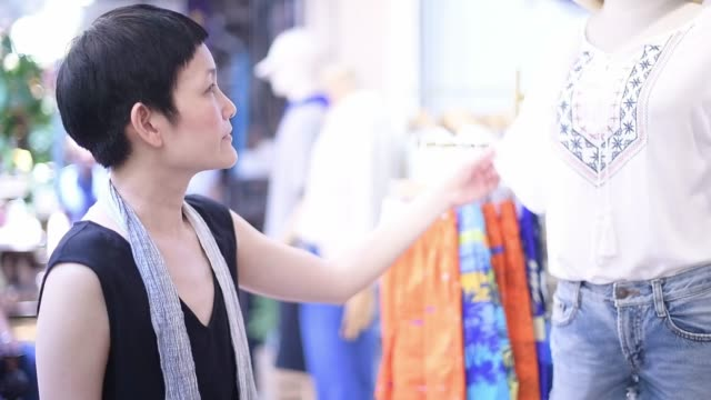woman shopping for beautiful clothes - boutique stock videos and b-roll footage