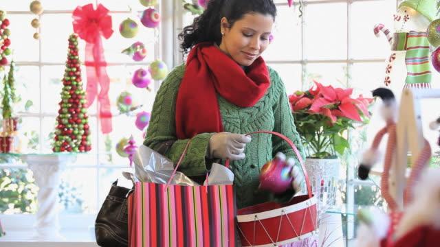 ms pan woman shopping for christmas ornaments in gift shop / richmond, virginia, usa - ギフトショップ点の映像素材/bロール