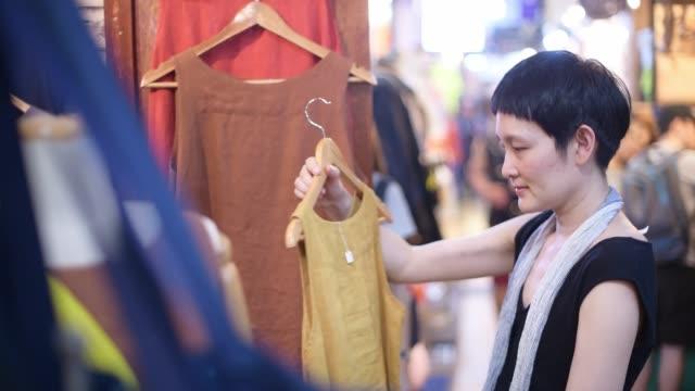 vídeos de stock, filmes e b-roll de compra da mulher para a roupa na zona exterior da alameda de compra. a senhora asiática com sentimento feliz compra a camisa colorida na loja - mercado das pulgas