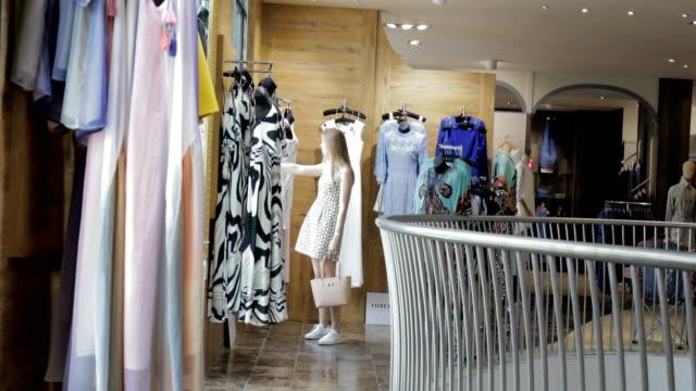 woman shopping for dresses - abbigliamento video stock e b–roll