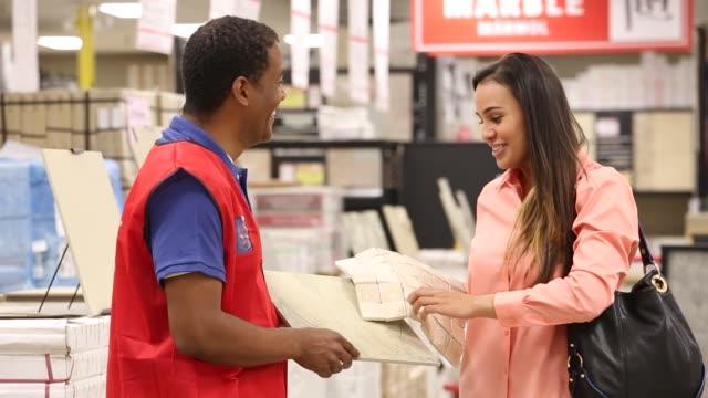 vidéos et rushes de woman shopping for marble in home improvement store - vendeur