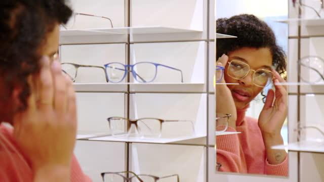 vídeos de stock e filmes b-roll de woman shopping for new eyeglasses at optical store - visão conceito