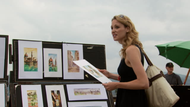 a woman shopping for small artworks - see other clips from this shoot 1150 stock videos and b-roll footage