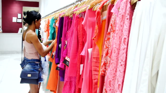 woman shopping in a clothes boutique - clothing store stock videos and b-roll footage