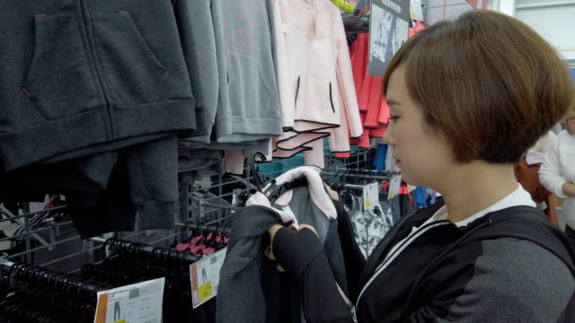vidéos et rushes de woman shopping in a clothing store - panier courses
