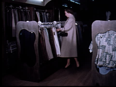 1965 ws woman shopping in clothing store, picking skirt off rack, and shoplifting by tucking it into her waste band and under her coat/ berkeley, california - shoplifter stock videos and b-roll footage