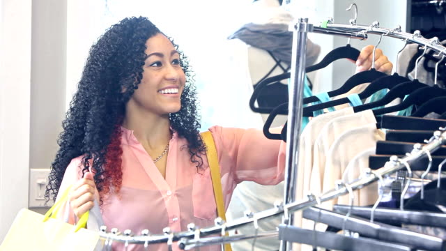 woman shopping in clothing store - eurasian ethnicity stock videos and b-roll footage