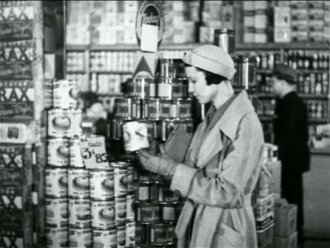 b/w 1938 woman shopping in grocery store selecting canned good / industrial - canned food stock videos & royalty-free footage