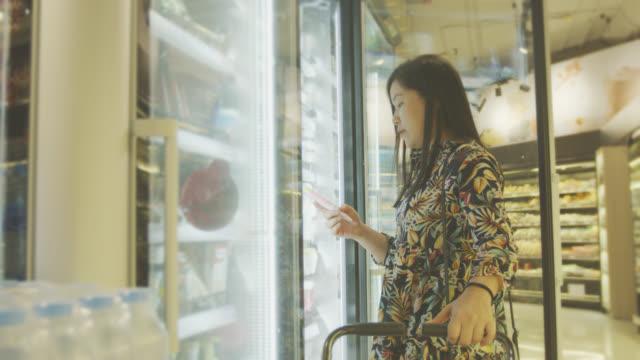 stockvideo's en b-roll-footage met vrouw winkelen in de supermarkt - roomijs