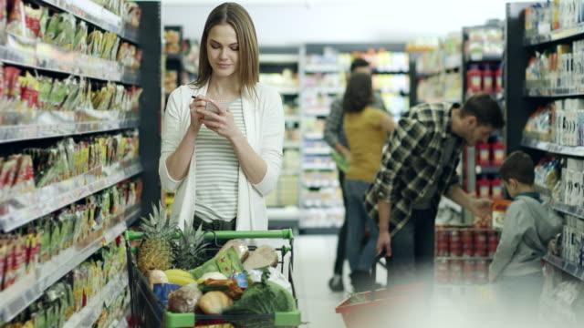 vídeos de stock, filmes e b-roll de mulher fazer compras no supermercado - atividade móvel
