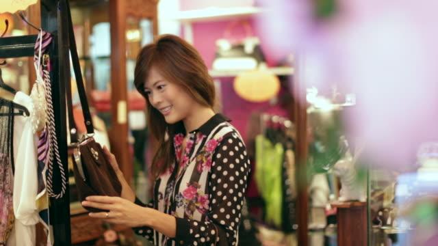 vídeos de stock, filmes e b-roll de ws woman shopping looking at handbag - antiquário loja