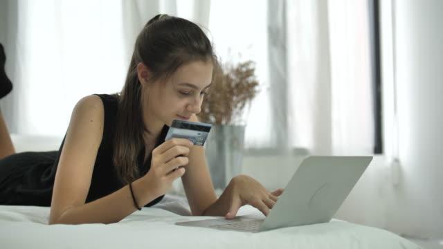 Kvinna shopping på Laptop med kreditkort i sovrum